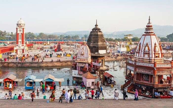 A view of temples by the Ganga river with devotees offering prayers