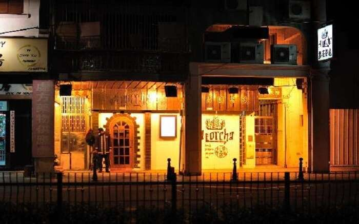 A well lit gate of a cafe at night