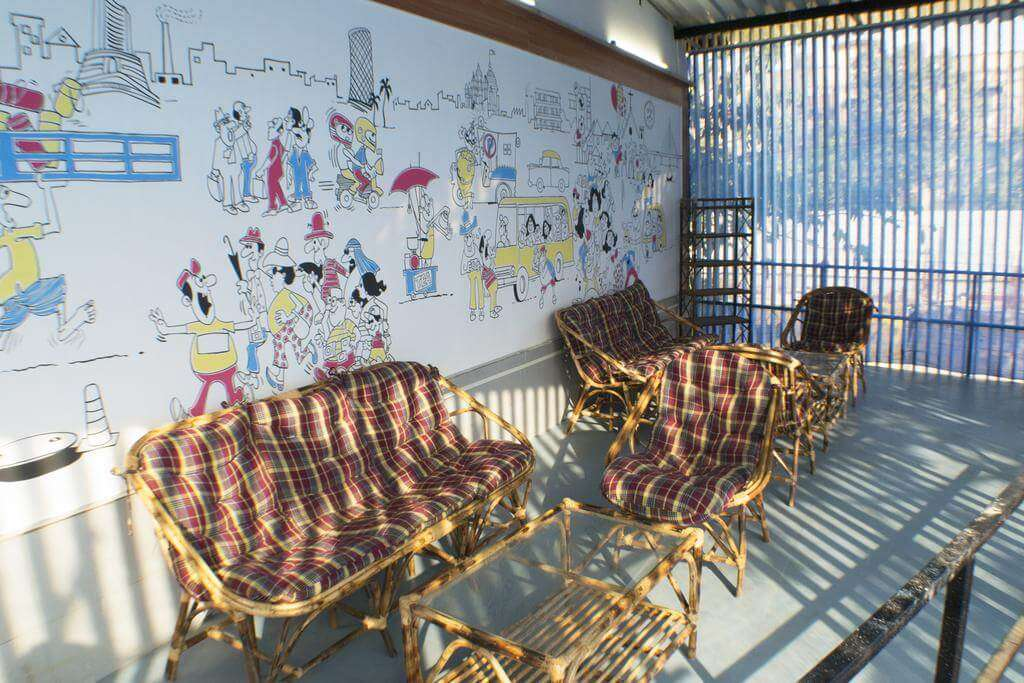 bamboo sofas in a room which has caricature on its white wall