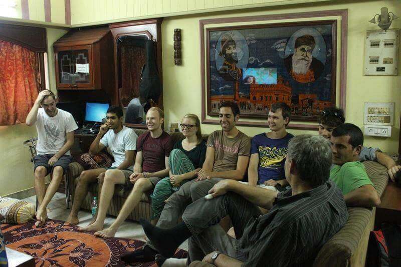 a bunch of travelers sitting in the living room of a hostel