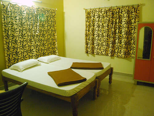 a room with curtains on window and a two beds with white bedsheet