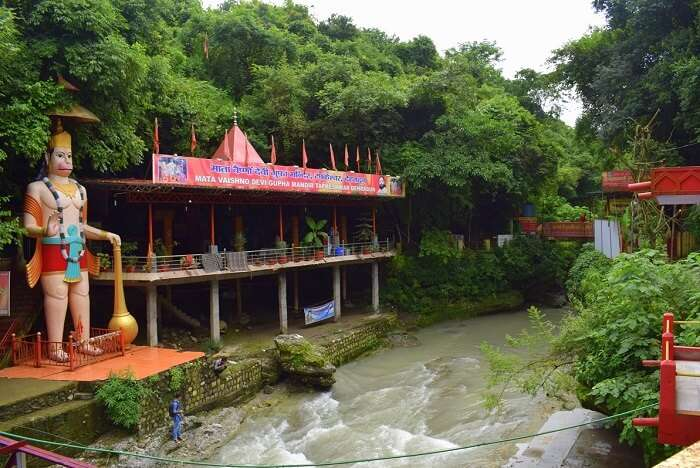 witness the enormous statue of hanuman at cave temple of Tapkeshwar Temple