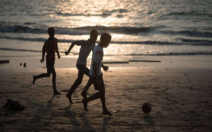 Three kids playing on a beach in evening