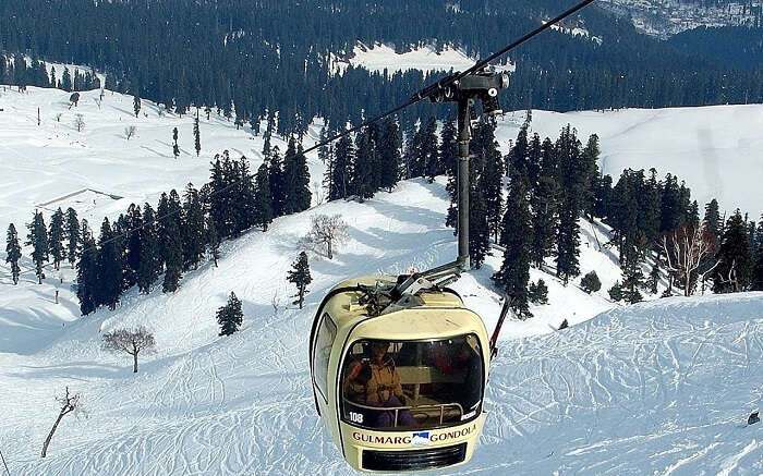 Travelers riding a cable car over a valley covered in snow in Gulmarg