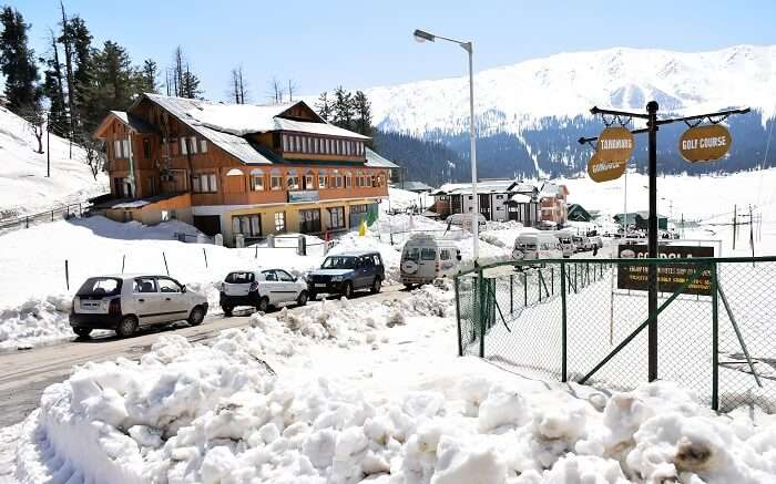 Vehicles parked outside a resort in Kashmir with snow all around