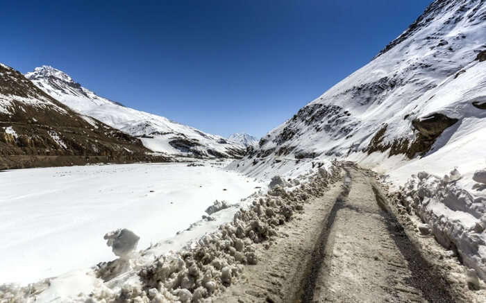 A sloppy road covered in snow leading to the Spiti valley