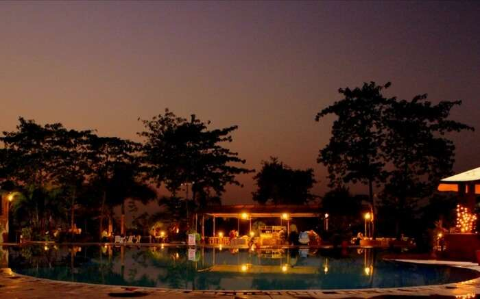 A pool view of River Winds Resorts in Mumbai at night