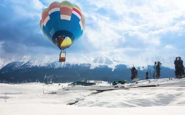 A hot air balloon flying over a village in Gulmarg in winter