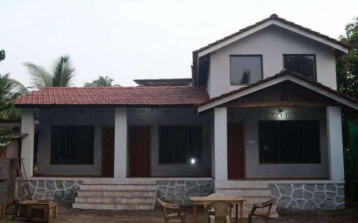 an elegant cottage with sloped roof in Alibaug