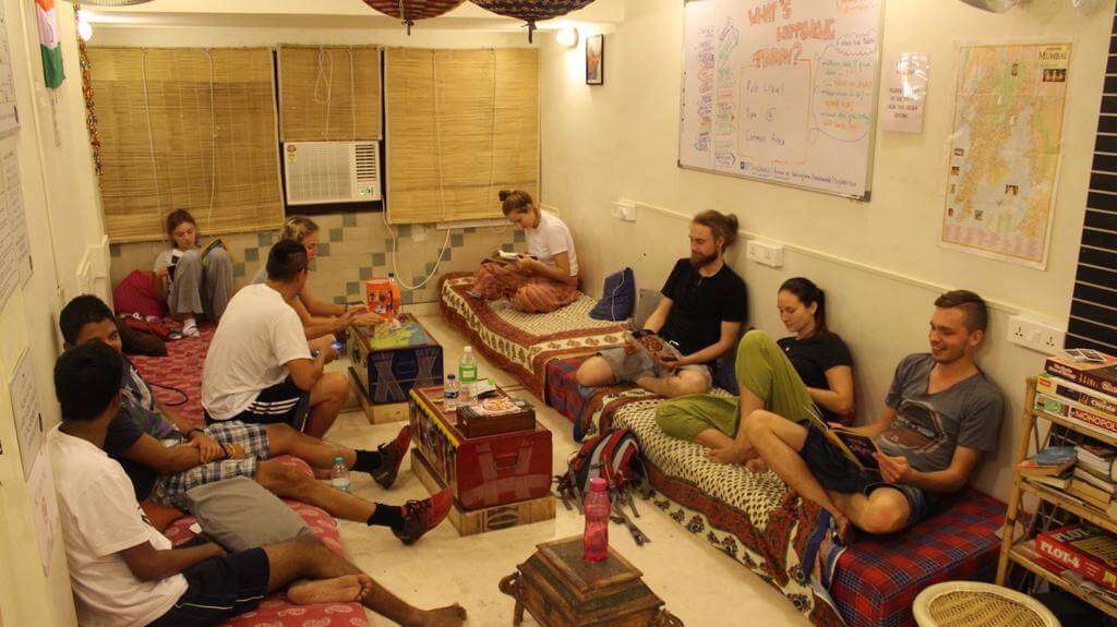 a group of travelers sitting in a living room of a hostel