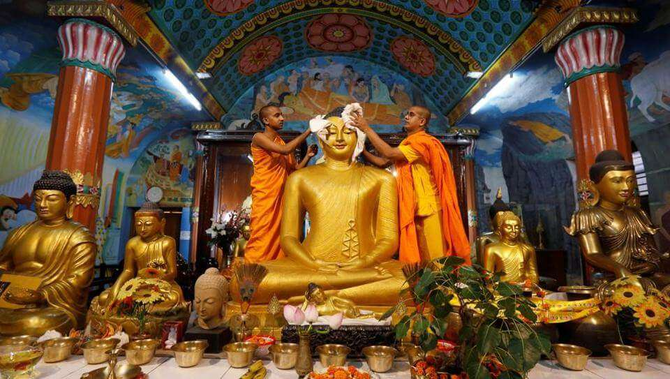 monks cleaning golden buddha statue