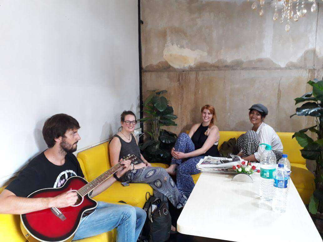 travelers playing guitar in a small living room of a hostel