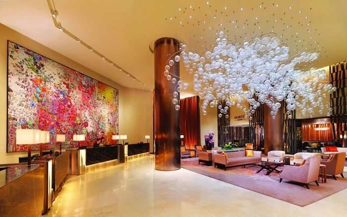A gorgeous reception area of a hotel with beautiful chandelier
