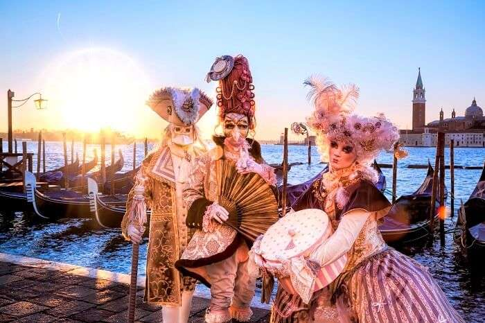 Venetian costumes pose in front of gondolas during the Venice Carnival days. The most famous festival in the world.