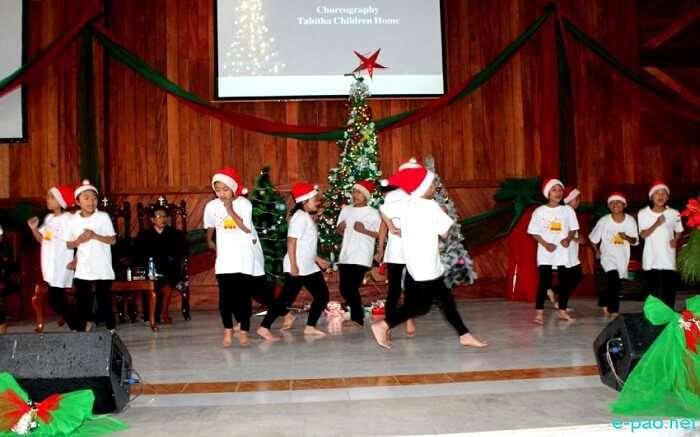Kids wearing santa caps on stage
