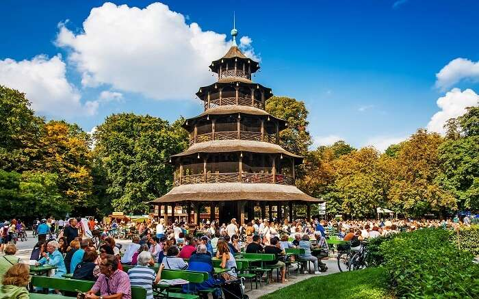 People sitting in a gorgeous garden with a huge pagoda like structure