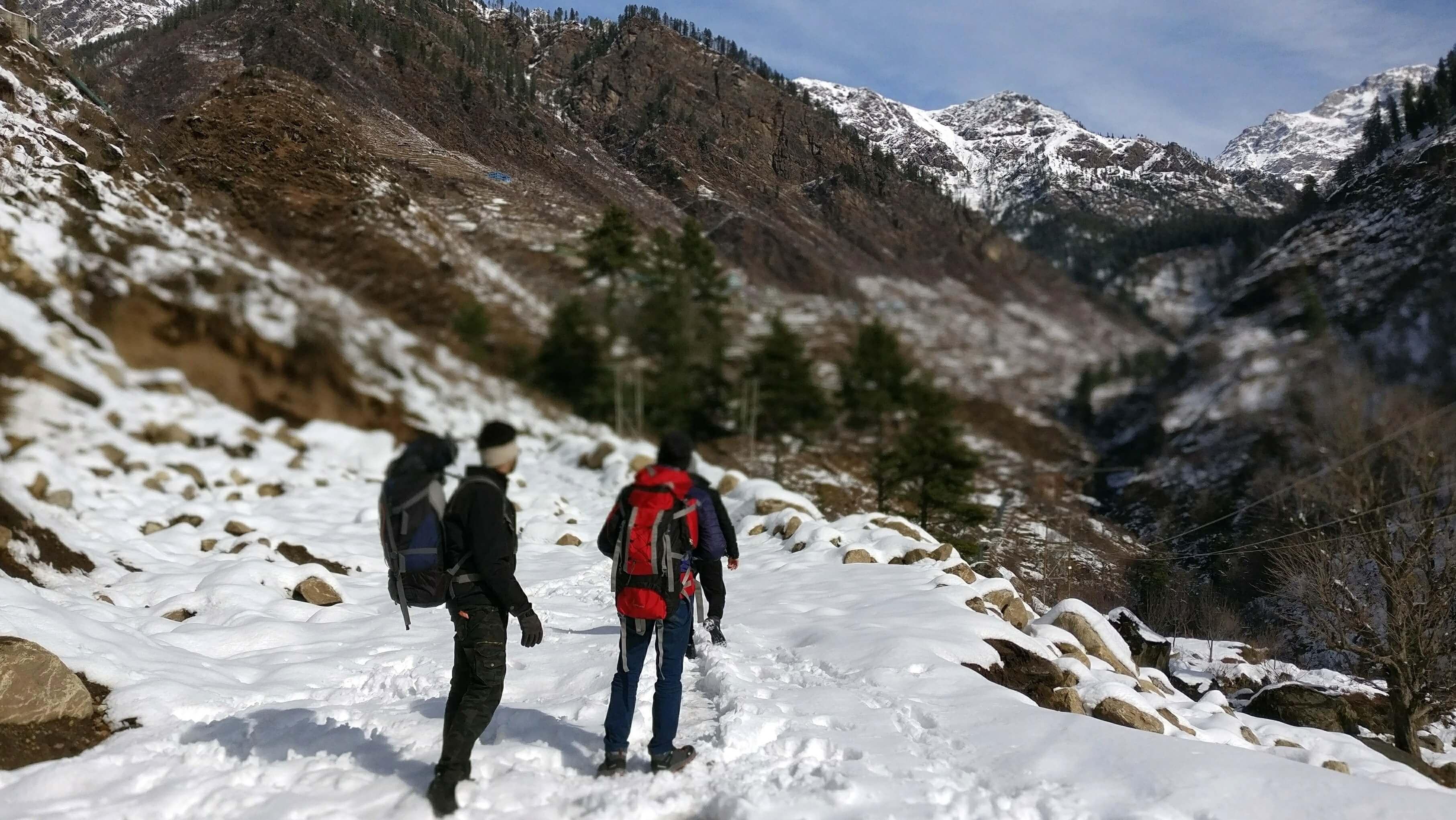 two men walking in snow in mountains