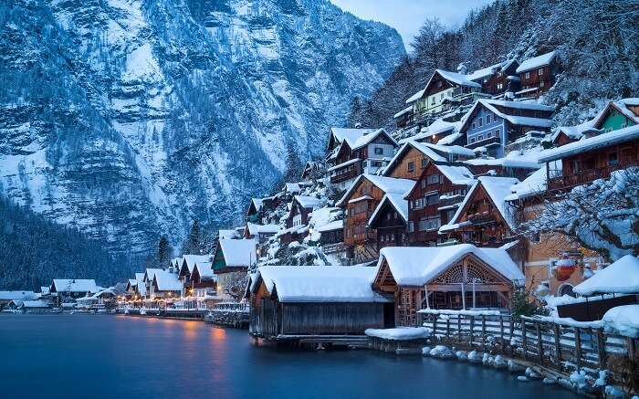 snow covered homes by a lake in austria
