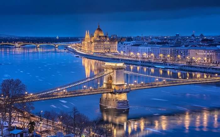 well lit Budapest parliament and bridge at night