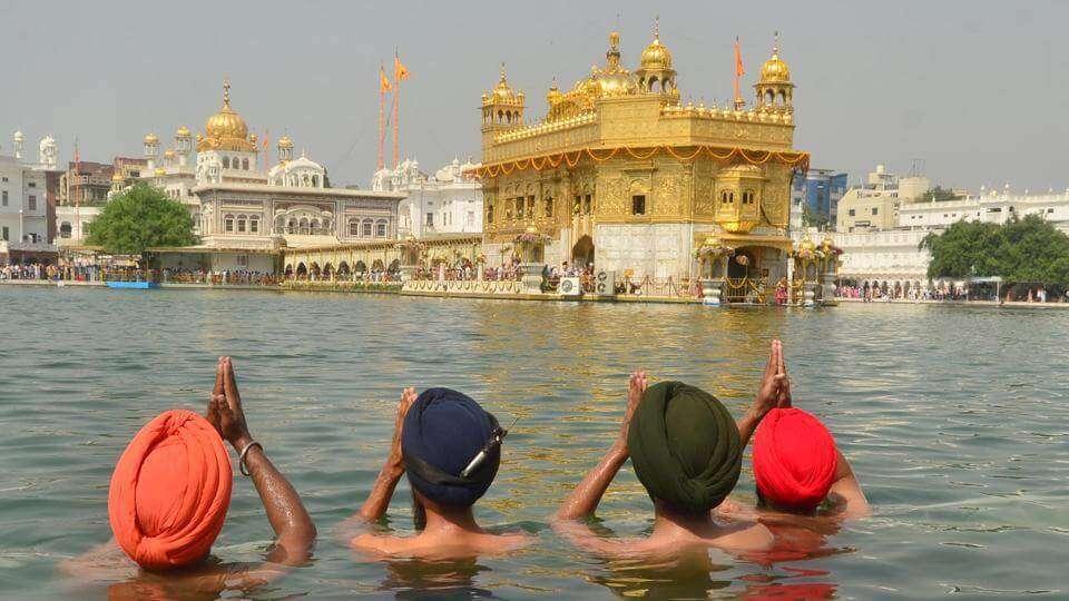 4 men praying in Golden Temple