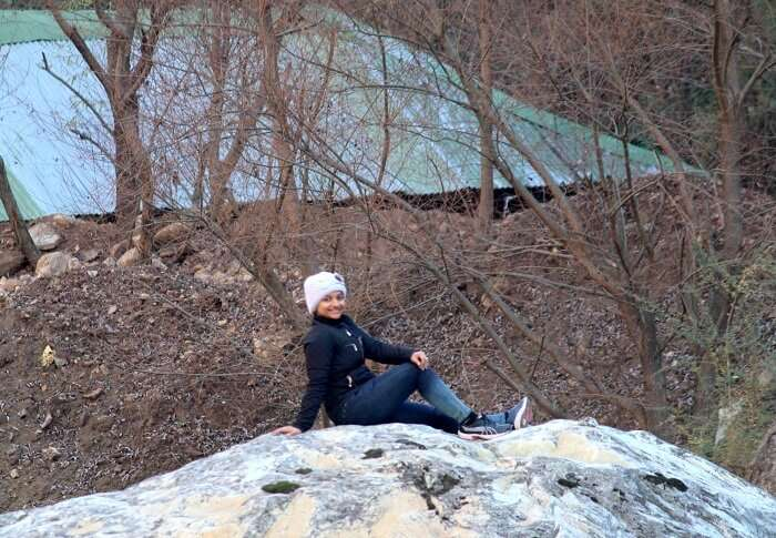 relaxing on a rock in tirthan