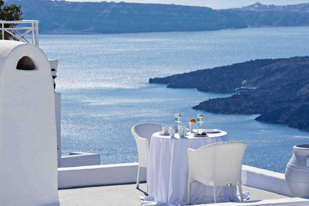 white table and chairs on a terrace overlooking caldera