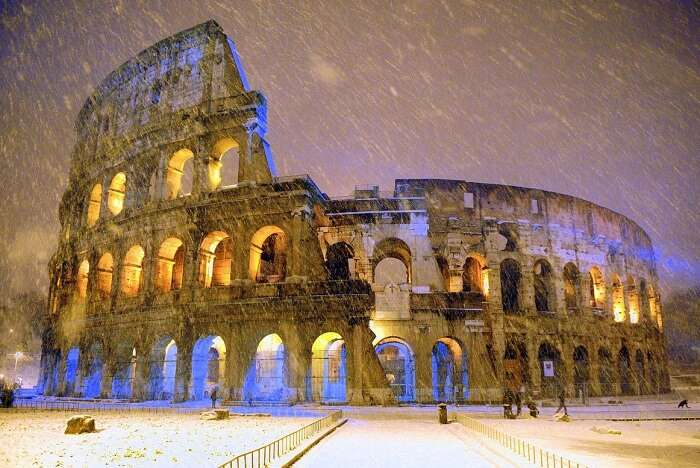 The ancient Colosseum is seen during an heavy snowfall late in the night in Rome
