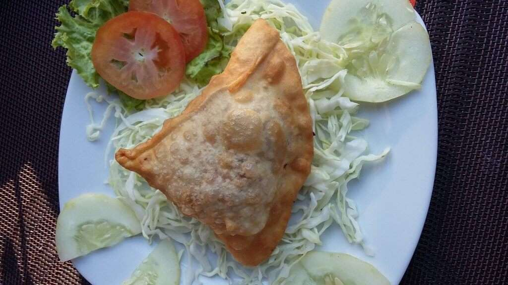 a samosa served with cabbage and tomato
