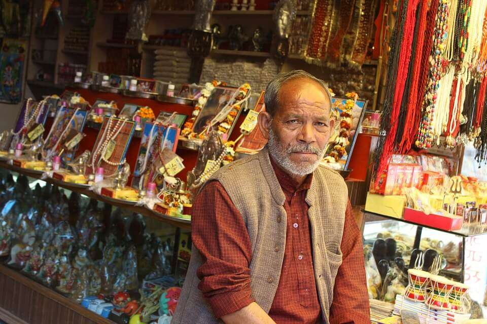 an old man sitting at his shop