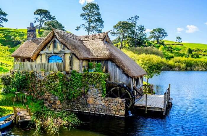 a beautiful Hobbit house by a lake