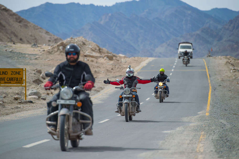 men riding bike on the roads of ladakh