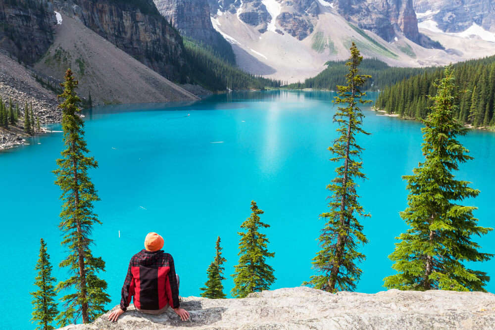a woman sitting on rock over looking a gorgeous lake in Banff National Park