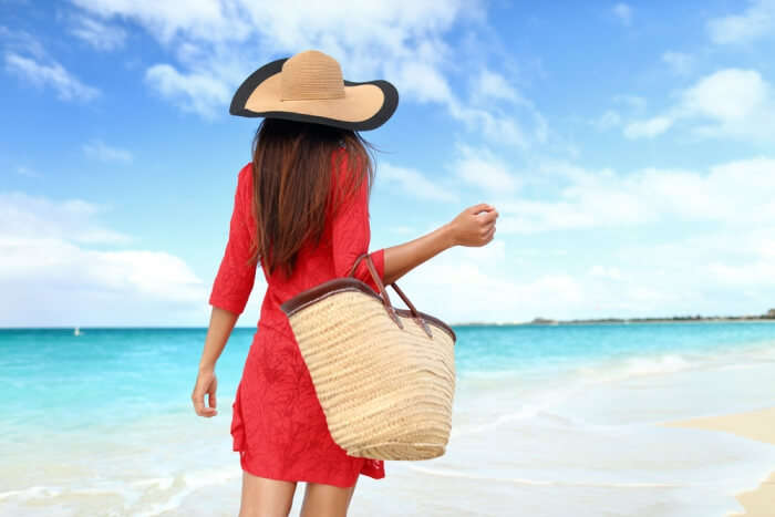 girl carrying bag to the beach
