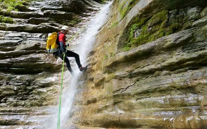 A man doing waterfall rappelling