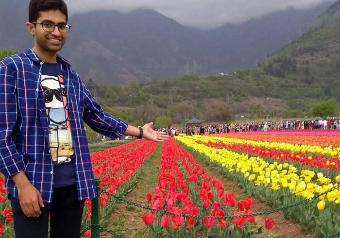 man standing in tulip garden