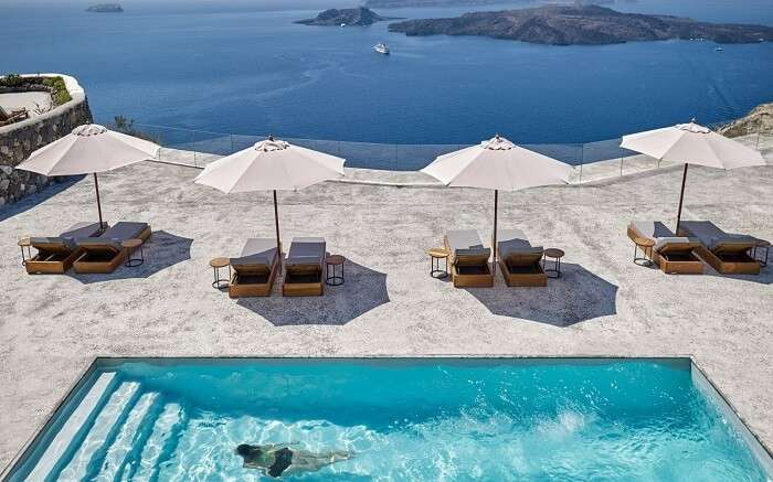 Sundecks and sun umbrella near the outdoor pool in a resort
