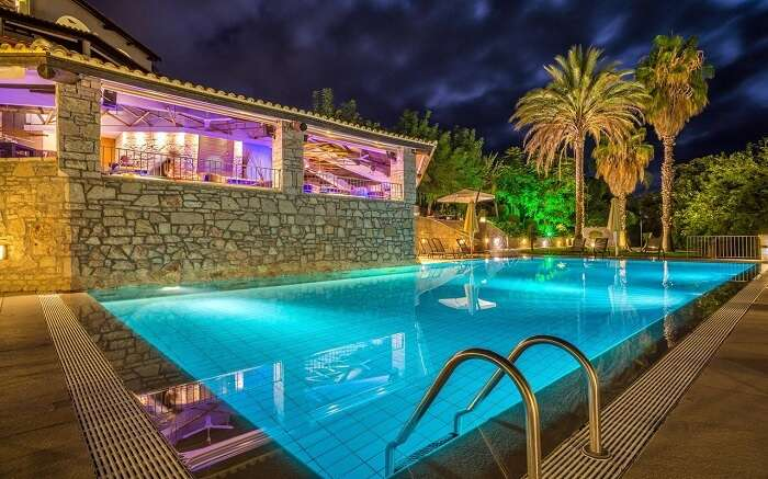 a beautifully lit outdoor pool in a resort