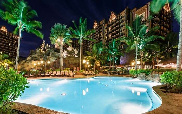 a well lit outdoor swimming pool in a resort
