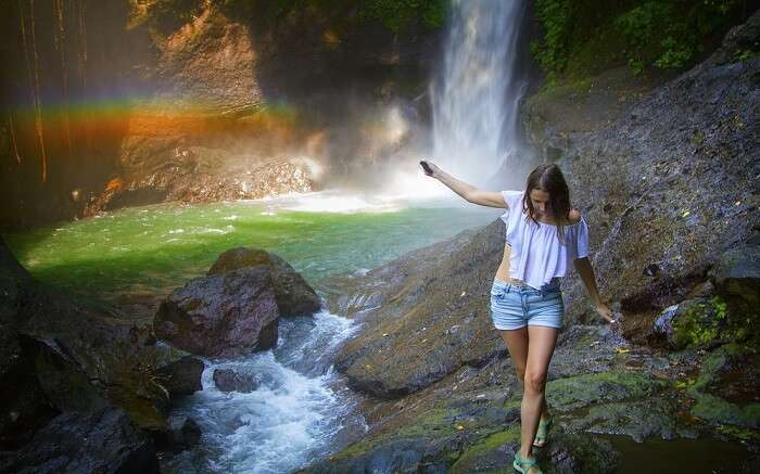 a women walking along a rainbow waterfall