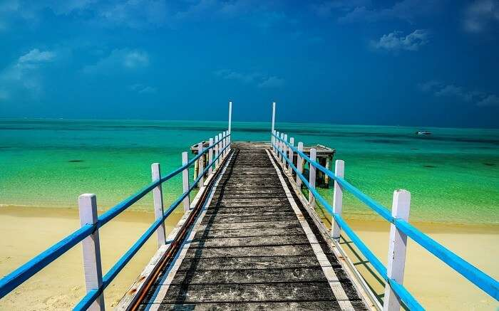 a wooden bridge leading to a beach in Kadmat Island