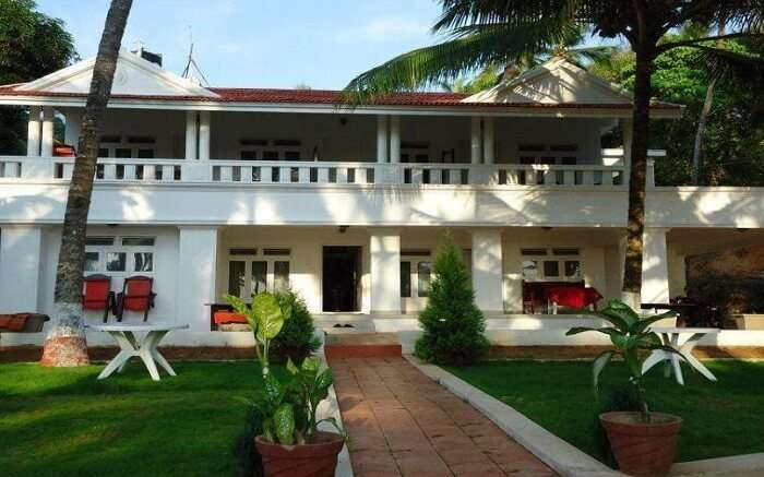 beautiful white Malabar Beach Resort with green lawn