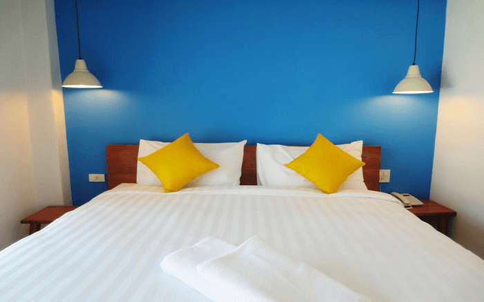 blue wall, yellow pillows in a room of Sleep Whale Express