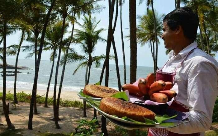 helper at Chera Beach Resort carrying freshly made food