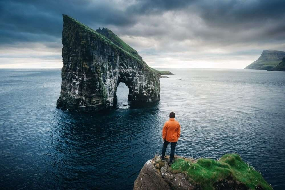a man standing at the edge of an ocean