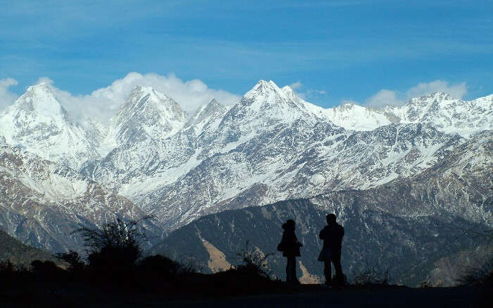 two travelers standing against the snowcovered mountains
