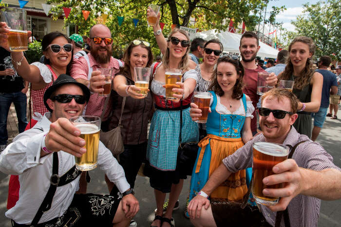 People posing with beer glasses at the Marchfest in NZ