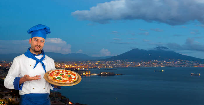 A chef holding pizza in Naples, Italy