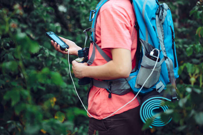 A traveler with a back pack using power-bank to charge his phone