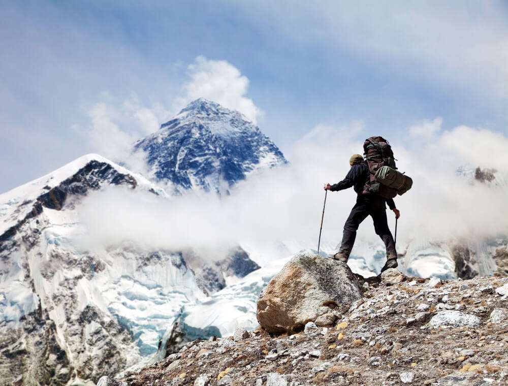 a man trekking in snow covered mountains