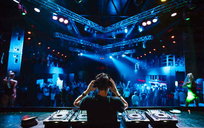 A DJ playing music for the audience at a club on a DJ Night